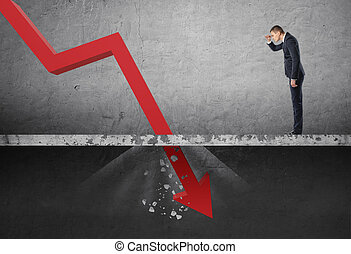 Businessman looking down at the falling red arrow destroying...