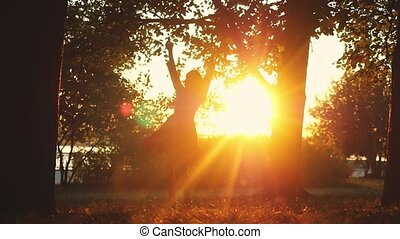 Joyful girl spinning around in autumn park during sunset on...