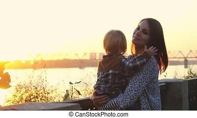 Mom holding her little son on promenade they touch the sun in slowmotion on sunshine background. 1920x1080