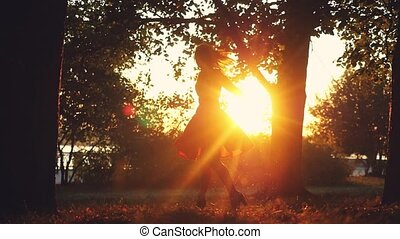 Joyful girl spinning around in autumn park during sunset on...