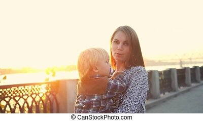Happy family. Mom holding her little son walking together on promenade in Sunny day during sunset in slowmotion.