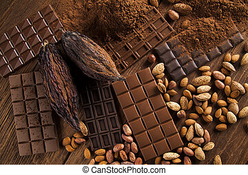 Chocolate bar, candy sweet, cacao beans and powder on wooden...