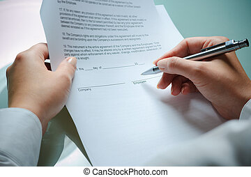 employment agreement - female hands filling out employment...