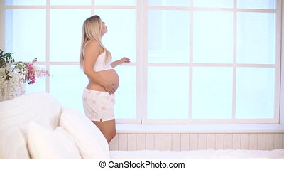 smiling pregnant woman caressing the belly against the...
