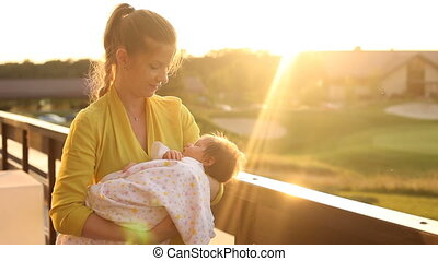 Woman dandling her baby - Young beautiful woman in yellow...