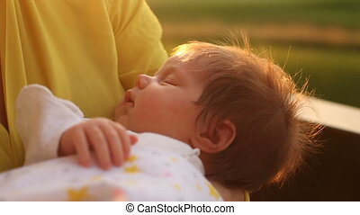 Baby sleeping on mother's hands - Little cute baby in pink...