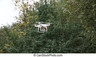 Drone with camera while flying in the forest. Unmanned aerial copter flight.