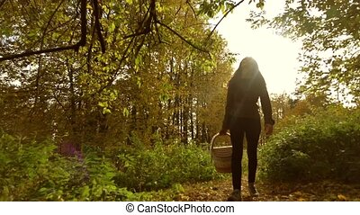 Young woman walking through autumn forest holding a picnic...