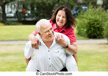 Senior Man Piggybacking His Wife - Portrait Of A Happy...