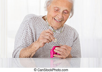 Senior Woman Inserting Coin In Purse - Happy Senior Woman...