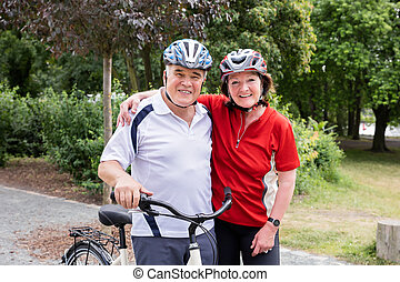 Portrait Of Smiling Couple With Bicycle - Portrait Of...
