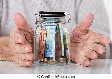 Senior Woman's Hand Protecting Money Jar - Close-up Of...