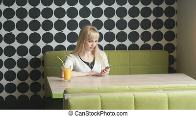 Girl texting sms using mobile phone in cafe