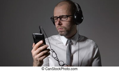 Businessman in a shirt and big headphones, listening to...
