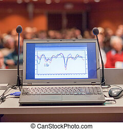 Computer and microphone on rostrum at business event. -...