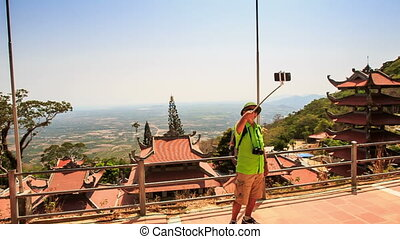 Man Makes Selfie against God Statues Gallery in Ta Cu Temple...
