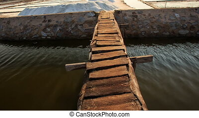 Wooden Bridge over Canal to Salt Heaps at Lakes in Vietnam -...