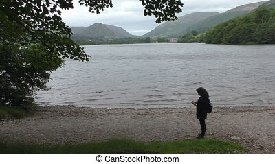 Woman taking picture of Grasmere la - Woman on the shore of...