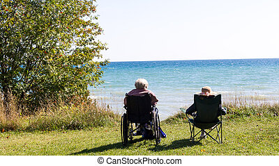 Two senior people sitting on the beach.