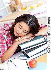 Tired asian student sleeping on her books in the kitchen