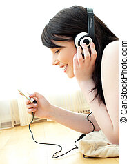 Jolly young woman listen to music lying on the floor