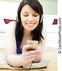 Charming young woman listen to music lying on the floor