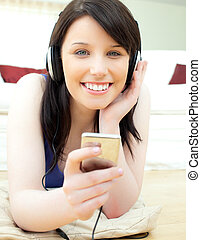 Glowing young woman listen to music lying on the floor