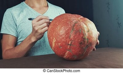 Guy in white shirt draws face on pumpkin jack o lantern with...