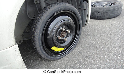 Car flat spare wheel on highway