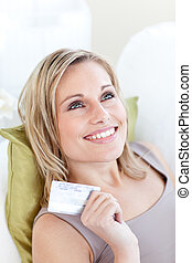 Cheerful caucasian woman holding a card sitting on a sofa
