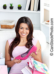 Cheerful young asian woman holding a shoe sitting between...