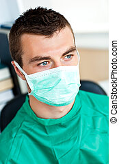 Serious male surgeon with mask and scrubs sitting in his...