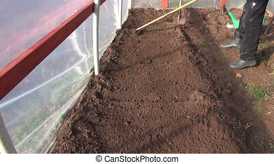Gardener evening out soil - Smoothing out soil on sunny...