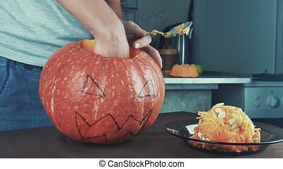 Male hands scooping out seeds and contents of pumpkin. Halloween theme, jack lantern. Medium shot 4k