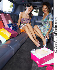 women shopping in limousine - women in limousine trying on...