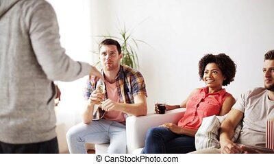 friends with popcorn and drinks talking at home -...