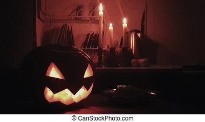 Halloween Jack o lantern with burning candle on a table in dark kitchen