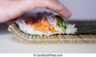 sushi rolls making process with man's fingers - sushi rolls...