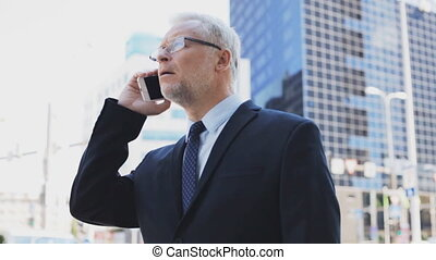 senior businessman calling on smartphone in city - business,...