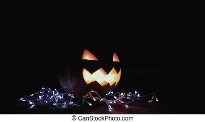 Halloween Jack o lantern with burning candle inside lay upon...