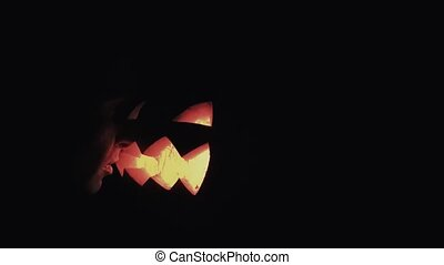 Young guy looks on burning candle inside of carved pumpkin jack o lantern face to face close up 4k