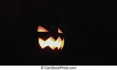 Halloween Jack o lantern with burning candle on a table in dark kitchen 4k