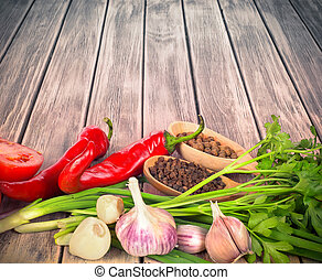 fresh vegetables with spices on a wooden background