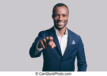 I choose you! Handsome young African man in smart casual jacket pointing you and smiling while standing against grey background
