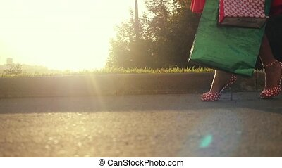 Shopaholic woman in beautiful dress holding many shopping bags walking on the street through the sun during sunset in slowmotion. View profile 1920x1080