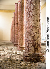 Antique marble columns resting on stone floor. - Antique red...