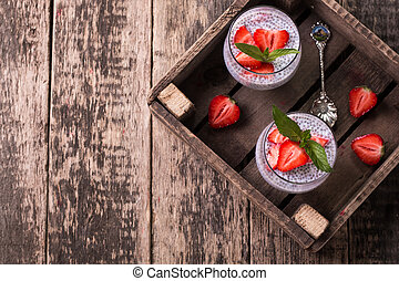 chia seed pudding with strawberries and min on wooden...