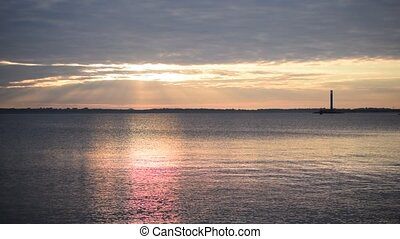 Colorful sunrise over water with lighthouse far off -...