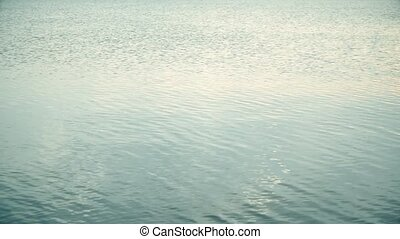 Rock skips across calm water surface leaving ripples and...
