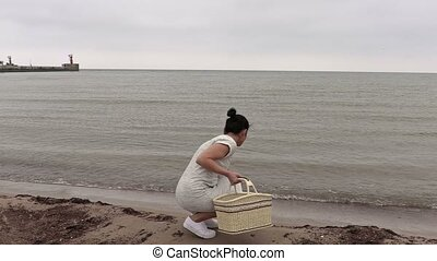 Woman with basket near sea